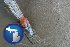 michigan map icon and smoothing a concrete surface with a trowel