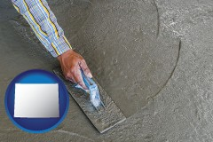 wyoming map icon and smoothing a concrete surface with a trowel